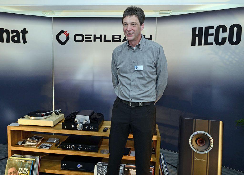 Entwickler Martin Groß mit den Messeneuigkeiten: links-hinten der Hybrid-Vollverstärker Magnat RV-4, rechts lugt dei Heco Direkt Einklang ins Bild