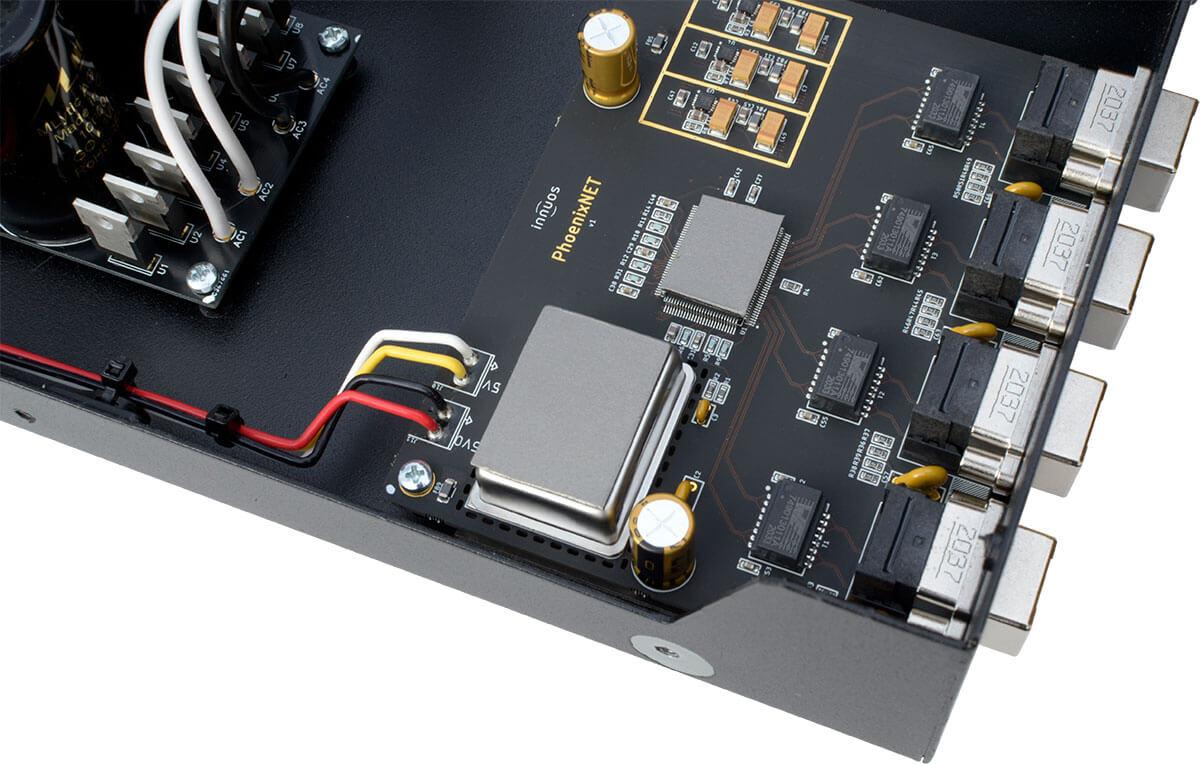 Das größere der zwei grauen Kästchen ist die OCXO-Clock, das kleinere darüber der Switch-Chip. Gut zu sehen: Hinter den LAN-Buchsen folgen vier Trenntrafos (die schwarzen Kästchen)